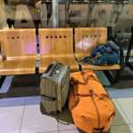 Luggage near a wooden bench at the airport
