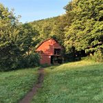 Overmountain Shelter red barn in a green grass field