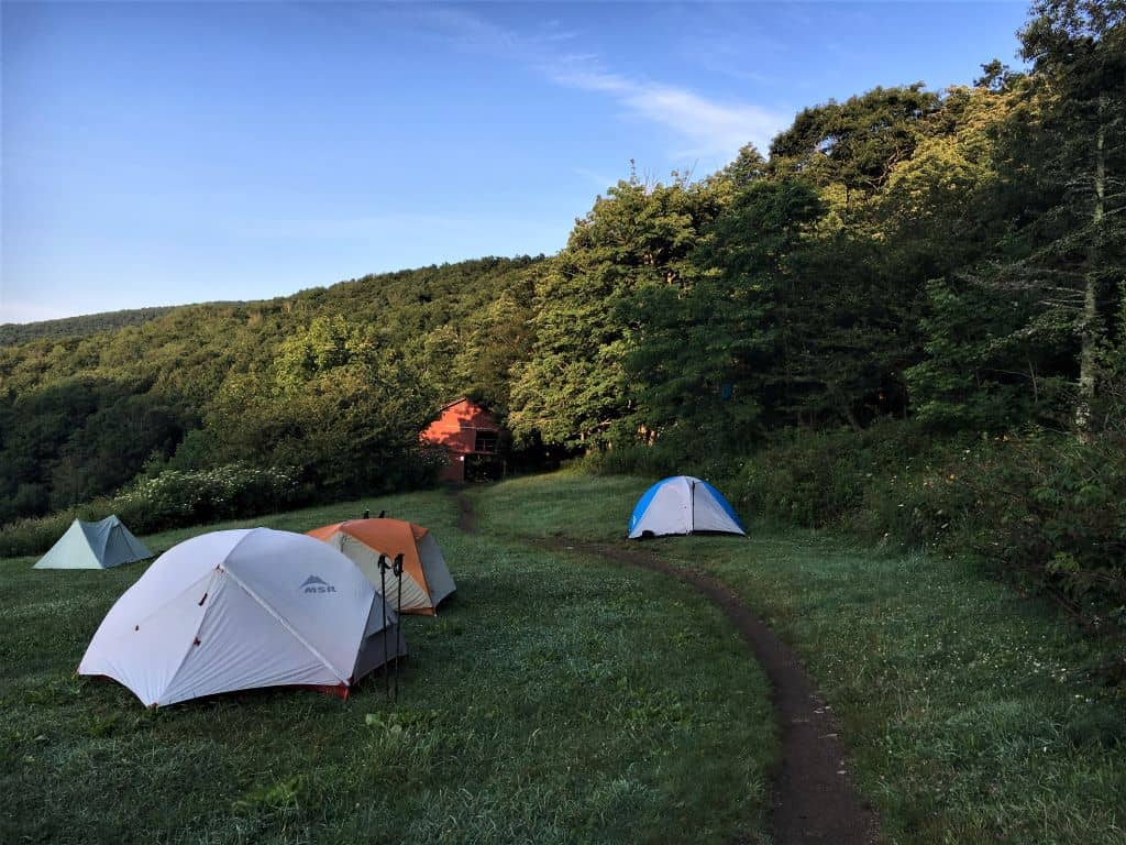 Tents pitched in a field with the red barn of Overmountain Shelter in the background